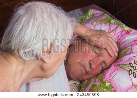 Elderly 80 Plus Year Old Man In A Home Bed And His Wife. Illness, Aging, Unhealthy Concepts
