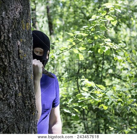 Maniac, The Killer In A Black Mask Is Behind A Tree With A Knife, Close-up, Killer With A Knife In T