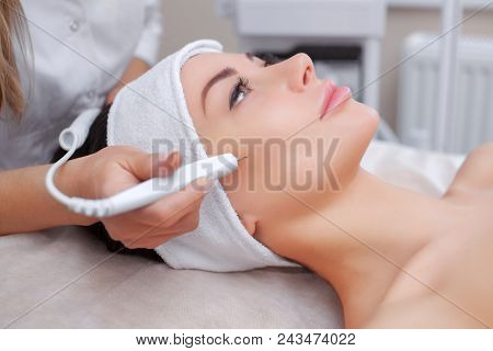 The cosmetologist makes the procedure treatment of Couperose of the facial skin of a beautiful, young woman in a beauty salon.Cosmetology and professional skin care. poster