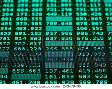 Concept Of Financial Data On A Monitor. Display Of Stock Market Quotes On Dark Background. Photo Of