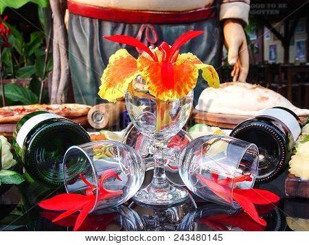 Wine Glasses, Flowers And Wine On The Table. Table Setting