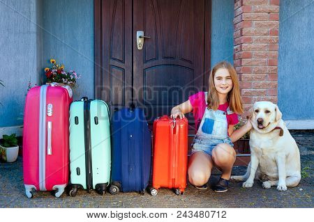 A Girl And A Large Labrador Dog Near Multi-colored Suitcases. Family Ready For The Travel For Summer