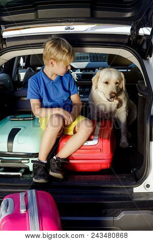 Boy Are Loading Multicolored Suitcases In The Trunk Of Car. The Kid Sits In The Open Trunk Of A Car