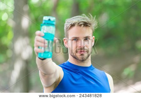 Man With Athletic Appearance Holds Bottle With Water. Man Athlete In Sport Clothes Training Outdoor.