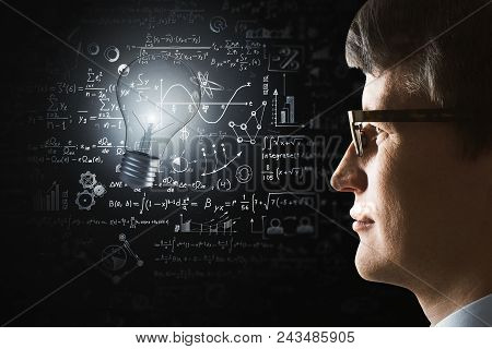 Side Portrait Of Young Businessman With Illuminated Lamp And Mathematical Formulas. Idea, Science An