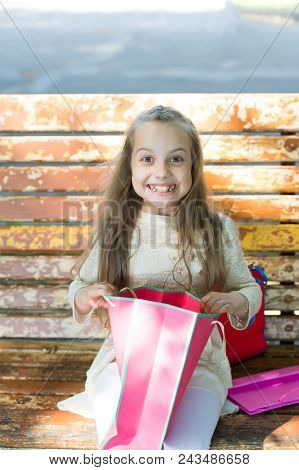Girl On Happy Face Unpacking Shopping Bags Or Presents, Bench On Background. Girl Surprised By Unexp