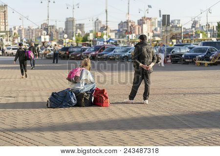 Girl With Suitcases On The City Street. A Young Woman With Suitcases Is Waiting For A Taxi On The Ci