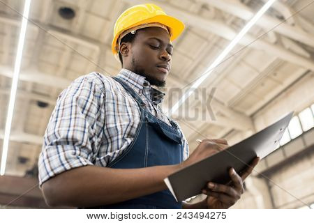 Waist-up Portrait Of Concentrated African American Technician Wearing Checked Shirt And Overall Taki