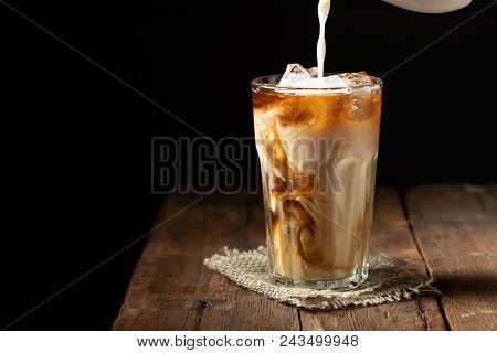 Ice Coffee In A Tall Glass With Cream Poured Over And Coffee Beans On A Old Rustic Wooden Table. Col