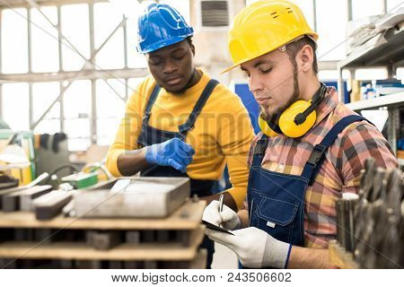 Bearded inspector wearing hardhat and overall taking notes while carrying out quality control at production department of modern plant, African American machine operator answering his questions poster