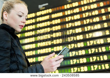 Young Woman At International Airport Looking At The Flight Information Board, Holding Smart Phone In