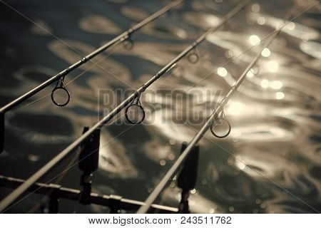 Rods, Lines On Blurred Water Surface, Fishing Equipment. Tackles For Angling In River, Lake, Pond, F