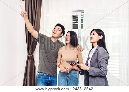 Real Estate Agent Holding Tablet And Talk With Young Couple In A House For Sale. Business And Real E