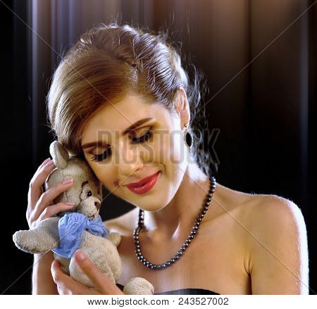 Woman in love. Beautiful girl with gift from boyfriend after first date. Children toy teddy bear as symbol childhood and romantic relationship on black background. First weeks of pregnancy.