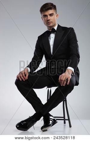 handsome young elegant man in tuxedo resting on a metal chair on light grey background