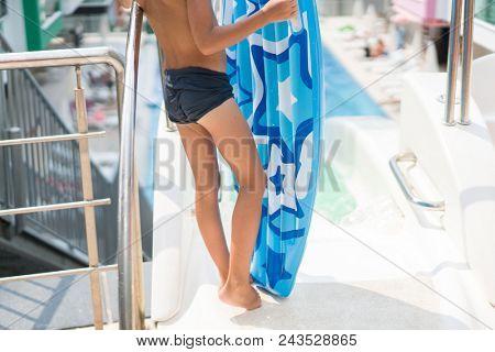 Children enjoying in summer resort at pool with air mattress