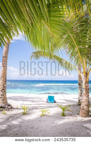 Looking Through Tropical Palm Trees On A White Sand Beach With A Sun Lounger For Relaxation On A Sun