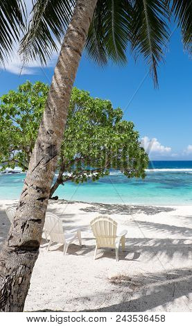 View Onto A White Sand Beach With Trees, Shade And Chairs For Relaxation On A Sunny Day, Looking Tow