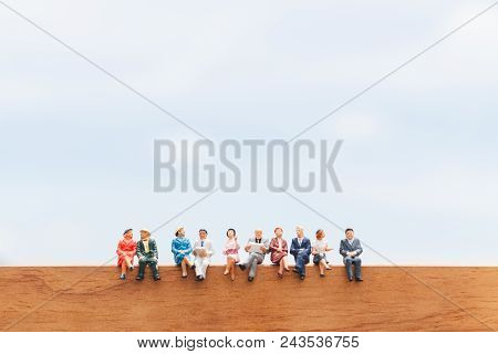 Miniature People: Group Of Business People Sitting On Wooden Floor With Blue Sky Background
