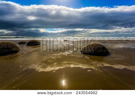 Boulders Moeraki - a group of large spherical boulders on the beach Koekokhe. Travel to New Zealand. Ocean evening tide. The popular tourist attraction. The concept of eco and photo tourism