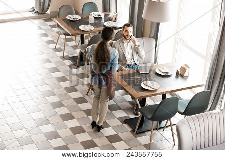 Rear View Of Waitress In Apron Waiting While Busy Man Finishing To Talk On Mobile Phone, Serious Han