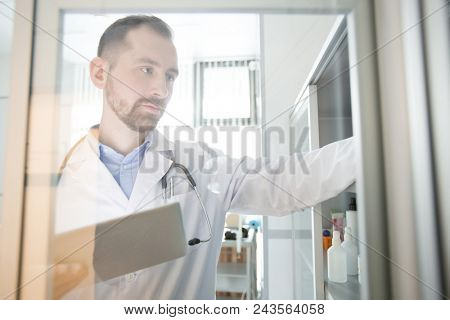 Young modern clinician with touchpad looking for something on shelf during work