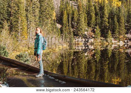 Woman tourist on trail near Bear Lake at autumn in Rocky Mountain National Park. Colorado, USA.