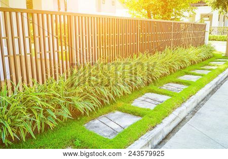 Concrete Pavement On The Outside Of The House Next To The Iron Fence, Slabs On Green Grass And A Fen