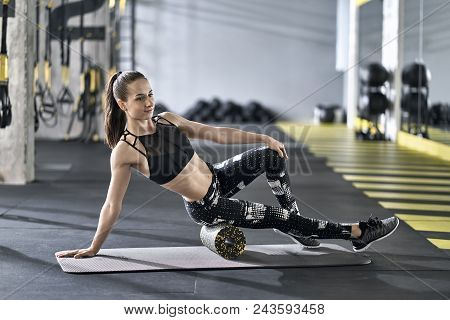 Beautiful Girl Is Training With A Black-yellow Foam Roller On The Gray Mat In The Gym. She Wears A B