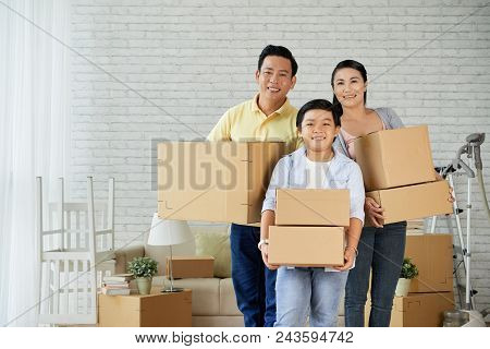 Joyful Asian Family Of Three Holding Moving Boxes In Hands And Looking At Camera With Toothy Smiles