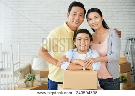 Loving Asian Family Of Three Posing For Photography With Wide Smiles While Distracted From Unpacking