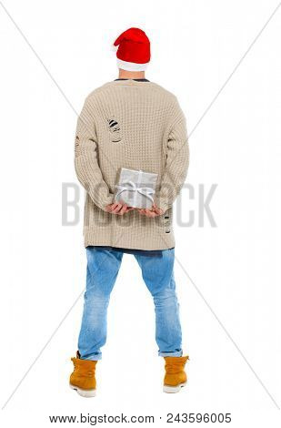 Back view of a man in a Christmas hat with a gift box. Rear view people collection.  backside view of person.  Isolated over white background. TA young guy is preparing a New Year's surprise