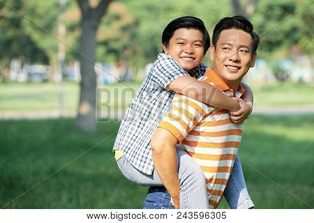 Loving Middle-aged Man Looking Away With Toothy Smile While Giving Piggyback Ride To Little Son, Pic