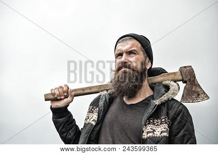 Hipster With Beard On Serious Face Carries Axe On Shoulder Sky On Background, Copy Space. Lumberjack