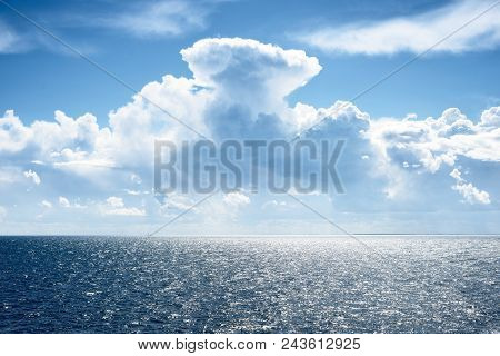Seascape Of A Baltic Sea With Very Distant Ship Silhouettes Against Blue Sky And Beautiful Clouds