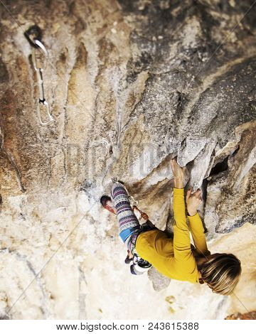 Woman Rock Climber. Rock Climber Climbs On A Rocky Wall. Woman Makes Hard Move.