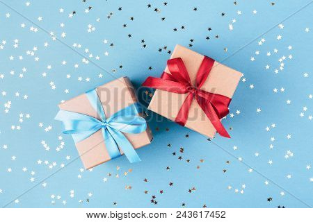Two Gift Boxes Wrapped In Kraft Paper And Tied With Ribbon On Blue Background Decorated With Confett