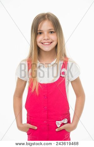 Child smiling with long blond hair. Small girl smile in pink jumpsuit isolated on white. Kid model in fashionable overall. Fashion style and trend. Happy childhood and childcare. poster
