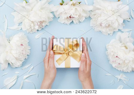Womans Hands Giving Gift Or Present Box Decorated White Peony Flowers On Pastel Table Top View. Flat