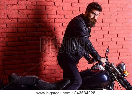 Hipster, Brutal Biker On Serious Face In Leather Jacket Gets On Motorcycle. Man With Beard, Biker In