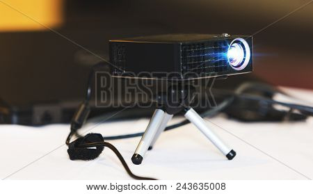 Black Projector With Tripod Installed On White Table, In Hall Or Seminar Meeting Room. Real Projecto