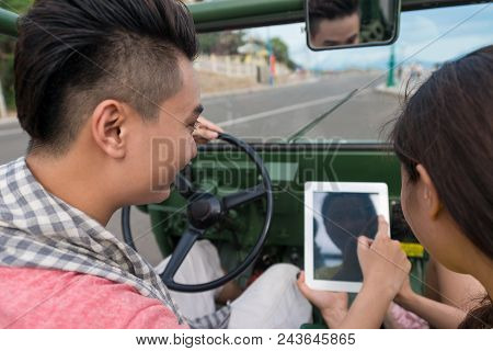 Young Couple Communicating By Touchpad While Driving A Car