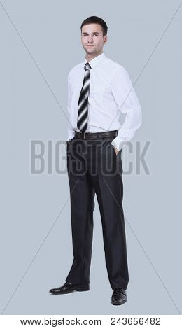 Full-length portrait of a confident businessman isolated on gray