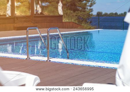 Swimming Pool With Stair And Wooden Deck At Hotel. Grab Bars Ladder In The Blue Swimming Pool. Summe