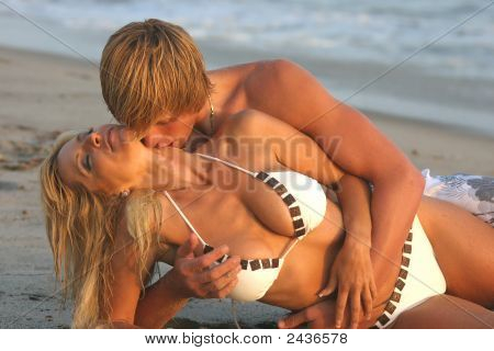 Couple Laying On Their Sides At The Beach Embracing