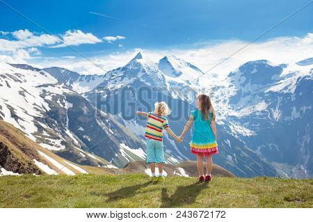 Children Hiking In Alps Mountains, Austria. Kids At Snow Covered Mountain Peak On Warm Sunny Spring