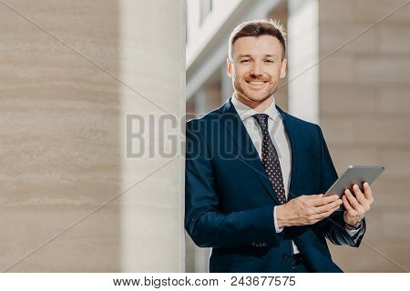 Horizontal Shot Of Happy Male Manager Dressed In Black Formal Suit, Uses Modern Tablet Computer For