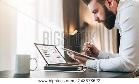 Young bearded businessman sitting at desk in front of laptop with graphis, charts, diagrams on screen, making notes in tablet computer. Freelancer works remotely. Student learning online. E-commerce. poster