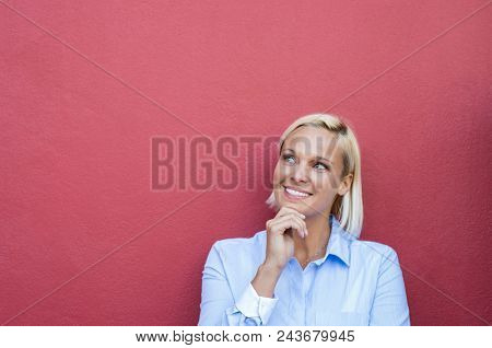 Closeup face of woman thinking with finger on chin. Happy pensive mature woman looking up and smiling on red wall with copy space. Portrait of blond thoughtful woman thinking on red background.