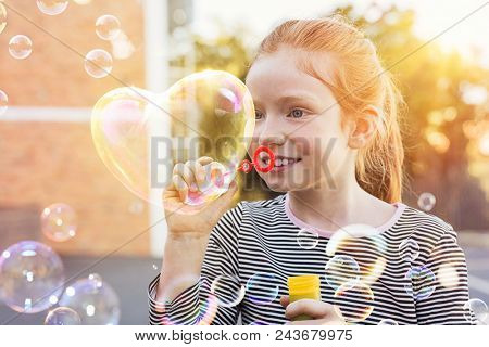 Portrait of funny little girl with red hair blowing heart shaped soap bubble at park. Portrait of cute girl blowing soap bubbles outside the school. Happy child playing with soap bubble at playground.